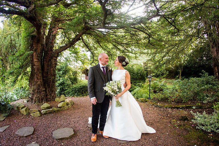 Newly-Wed couple embracing in the picturesque grounds of Horton Grange